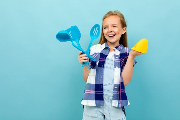Smiling european girl with cooking utensils in hands on light blue