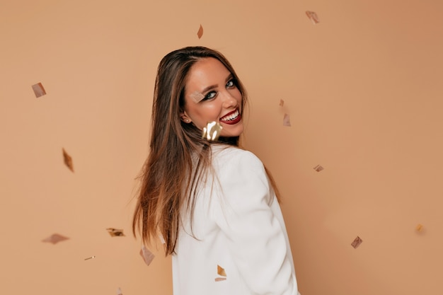 Smiling european lady dancing in studio over confetti. studio shot of beautiful female model