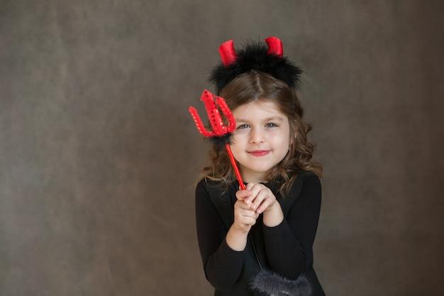Улыбающаяся европейская маленькая девочка в чертовом костюме хэллоуина с тремя зубцами