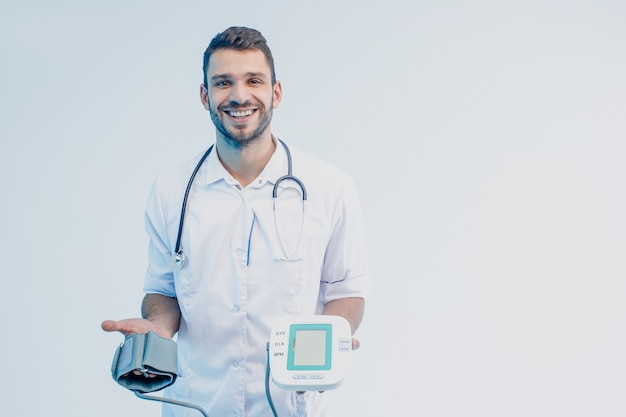 Улыбающийся европейский мужской доктор показывает цифровой тонометр. молодой бородатый человек со стетоскопом в белом халате. изолированные на сером фоне с бирюзовым светом. студийная съемка. копировать пространство