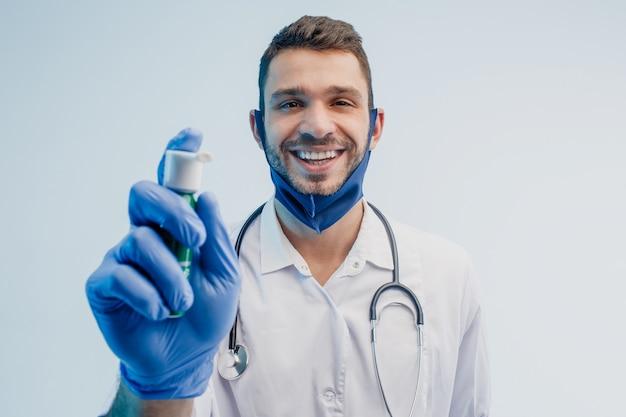 Улыбающийся европейский мужской доктор показывает ингалятор. молодой бородатый мужчина со стетоскопом в белом халате, защитной маске и латексной перчатке. изолированные на сером фоне с бирюзовым светом. студийная съемка