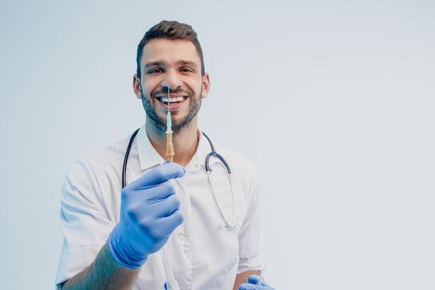Улыбающийся европейский мужской доктор показывает шприц. молодой бородатый мужчина со стетоскопом в белом халате с латексными перчатками. изолированные на сером фоне с бирюзовым светом. студийная съемка. скопируйте пространство.