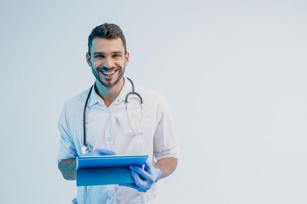 Улыбающийся европейский мужской доктор с цифровым планшетом. молодой бородатый мужчина со стетоскопом в белом халате с латексными перчатками. изолированные на сером фоне с бирюзовым светом. студийная съемка. скопируйте пространство.