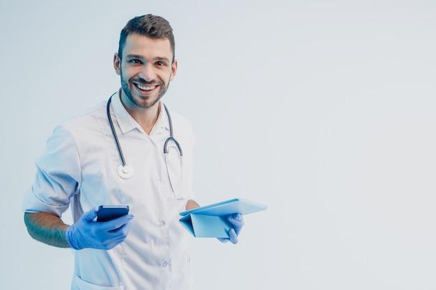 Улыбающийся европейский мужчина-врач с мобильным телефоном и цифровым планшетом. молодой бородатый мужчина со стетоскопом носит белое пальто с латексными перчатками. серый фон с бирюзовым светом. студийная съемка. скопируйте пространство.