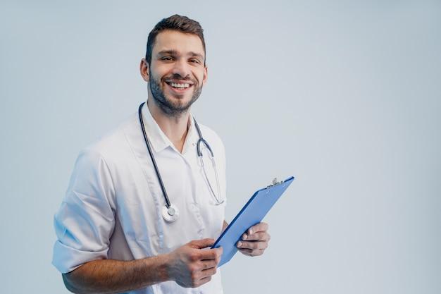 Улыбающийся европейский мужской доктор со стетоскопом и доской сзажимом для бумаги. молодой бородатый мужчина в белом халате. изолированные на сером фоне с бирюзовым светом. студийная съемка. скопируйте пространство.