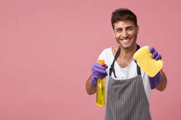 Smiling european male dressed in apron and rubber protective gloves holding sponge and detergent posing