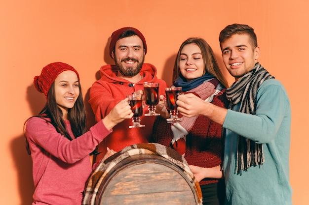 パーティーの写真撮影中にヨーロッパの男性と女性を笑顔。フォアグラウンドでホットホットワインとワイングラスを持ってスタジオフェストで友達を装った男たち。