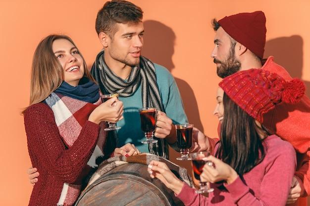 Улыбающиеся европейские мужчины и женщины во время партийной фотосессии. парни изображают друзей на фестивале в студии с бокалами с горячим глинтвейном на переднем плане.