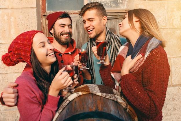 パーティーの写真撮影中にヨーロッパの男性と女性の笑顔。フォアグラウンドでホットグリューワインをワイングラスでスタジオフェストで友達を装った男。