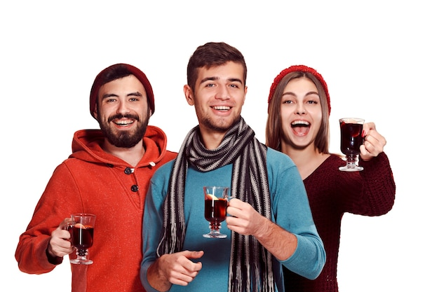 Smiling european men and women during party photoshoot. the guys posing as friends at studio fest with wineglasses with hot mulled wine on foreground.