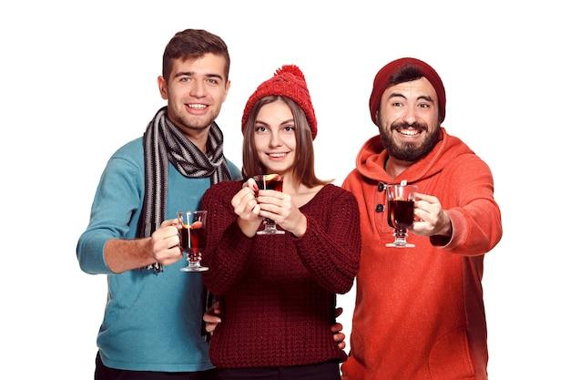 Uomini e donne europei sorridenti durante il servizio fotografico del partito. i ragazzi in posa come amici allo studio fest con bicchieri di vino con vin brulè caldo in primo piano.