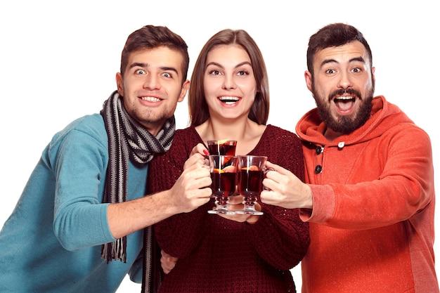 Uomini e donne europei sorridenti durante il servizio fotografico del partito. ragazzi in posa come amici allo studio fest con bicchieri di vino con vin brulè caldo in primo piano.