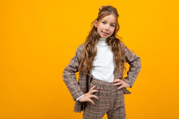 コピースペースと黄色でポーズ古典的な茶色のスーツで笑顔のヨーロッパの女子高生