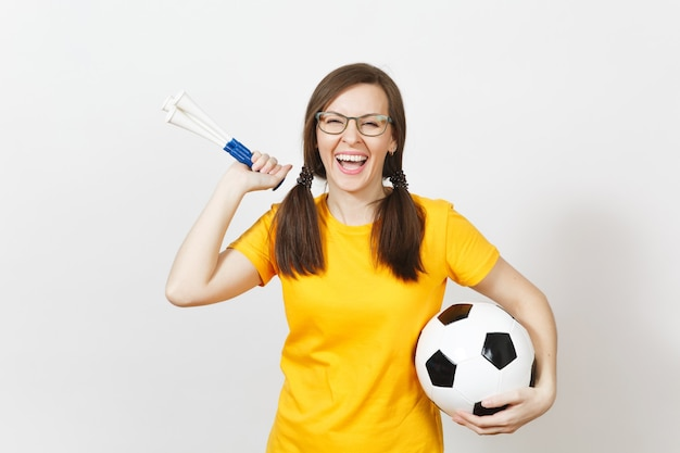 Smiling european woman, two fun pony tails, football fan or player in glasses, yellow uniform hold football pipe, ball isolated on white background. sport, football, health, healthy lifestyle concept.