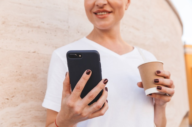 Smiling european woman wearing white t-shirt using black mobile phone, while standing against beige wall outdoor in summer and drinking coffee from paper cup