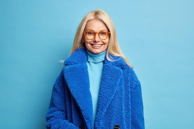 Улыбающаяся европейская женщина со светлыми волосами, одетая в синее зимнее пальто, имеет счастливое настроение, носит очки.