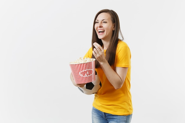 웃고 있는 유럽의 젊은 여성, 축구 팬, 노란색 유니폼을 입은 선수, 축구공, 흰색 배경에 격리된 팝콘 양동이. 스포츠, 축구, 응원, 팬들의 라이프스타일 컨셉입니다.