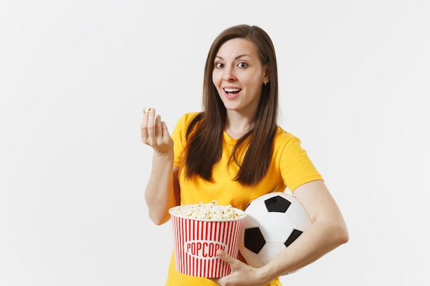笑顔のヨーロッパの若い女性、サッカーファンまたはサッカーボール、白い背景で隔離のポップコーンのバケツを保持している黄色の制服を着たプレーヤー。スポーツ、サッカー、応援、ファンの人々のライフスタイルのコンセプト。