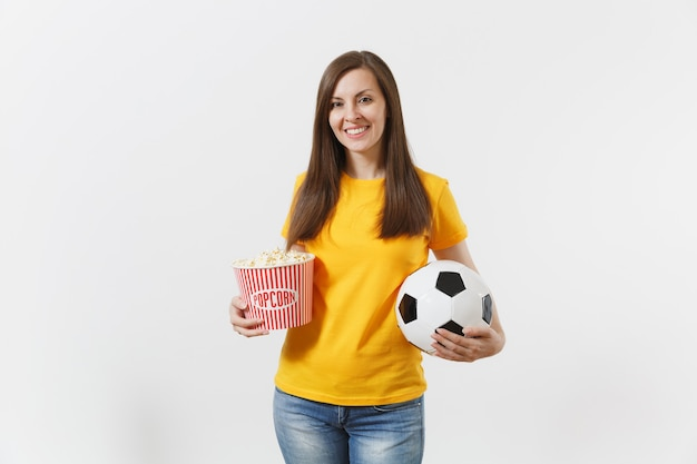 Smiling european young woman, football fan or player in yellow uniform holding soccer ball, bucket of popcorn isolated on white background. sport, play football, cheer, fans people lifestyle concept.
