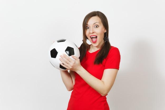 웃고 있는 유럽의 젊은 여성, 재미있는 조랑말 꼬리 두 개, 축구 팬 또는 흰색 배경에 격리된 고전적인 축구공을 들고 빨간색 유니폼을 입은 선수. 스포츠 플레이 축구 건강, 건강한 생활 방식 개념.