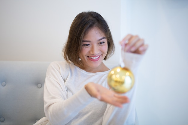 Smiling excited asian girl holding christmas ball