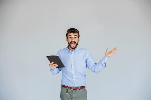 白い壁の前に立って、カメラを見ながらタブレットを保持している笑顔の興奮したひげを生やしたスーパーバイザー。ビジネスは完全に順調に進んでいます。