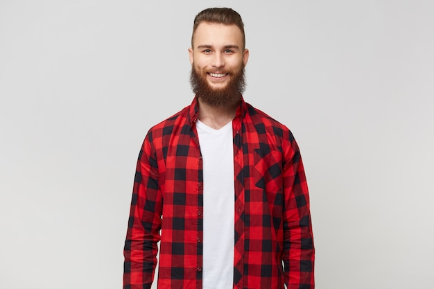 Улыбающийся возбужденный забавный молодой привлекательный бородатый мужчина, одетый в клетчатую рубашку, имеет счастливое радостное позитивное выражение лица, улыбается, изолирован на белом фоне