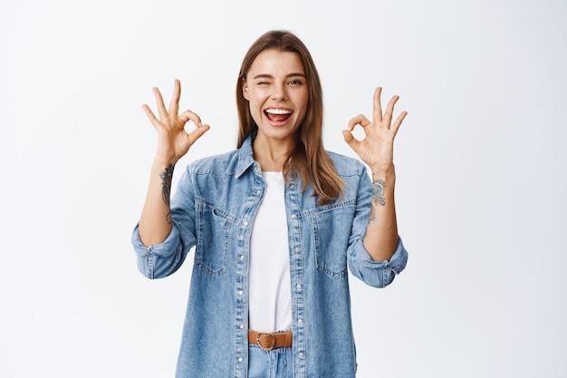 Sorridente ragazza eccitata che mostra segni ok e strizza l'occhio, dì sì o va bene, loda l'ottimo lavoro, bel gesto di lavoro, stando felice contro il muro bianco