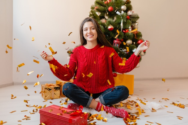 Улыбающаяся возбужденная красивая женщина в красном свитере сидит дома у елки, бросая золотые конфетти в окружении подарков и подарочных коробок