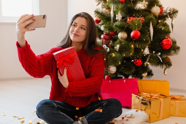 クリスマスツリーで自宅に座っている赤いセーターを着て、興奮したきれいな女性を笑顔でプレゼントやギフトボックスを開梱し、電話のカメラで自分撮り写真を撮る