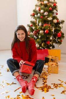 Улыбающаяся возбужденная красивая женщина в красном свитере сидит дома у елки, распаковывая подарки и подарочные коробки