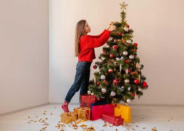 プレゼントやギフトボックスに囲まれたクリスマスツリーを飾る家に立っている赤いセーターで興奮したきれいな女性の笑顔