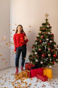 Donna graziosa emozionante sorridente in maglione rosso che si siede a casa all'albero di natale che getta coriandoli dorati circondati da regali e scatole regalo