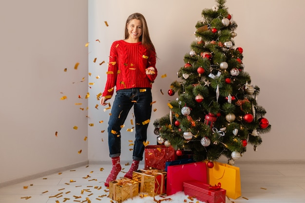 Smiling excited pretty woman in red sweater sitting at home at christmas tree throwing golden confetti surrounded with presents and gift boxes
