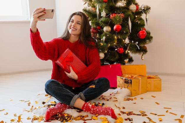 Sorridente donna graziosa eccitata in maglione rosso seduto a casa all'albero di natale disimballaggio regali e scatole regalo prendendo selfie foto sulla fotocamera del telefono