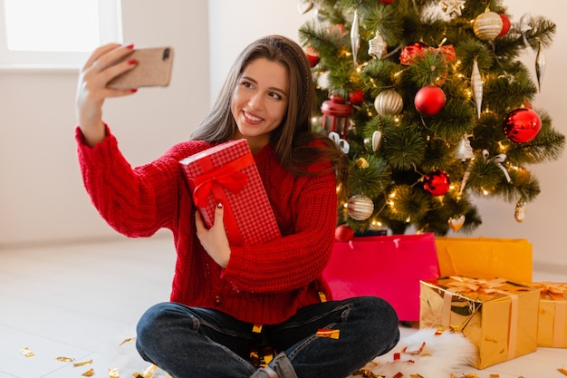 Smiling excited pretty woman in red sweater sitting at home at christmas tree unpacking presents and gift boxes taking selfie photo on phone camera