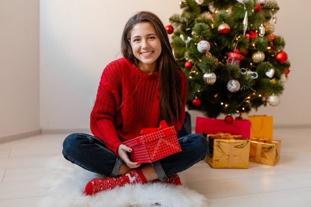 Sorridente donna graziosa eccitata in maglione rosso seduto a casa all'albero di natale disimballaggio regali e scatole regalo