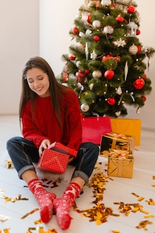 Smiling excited pretty woman in red sweater sitting at home at christmas tree unpacking presents and gift boxes