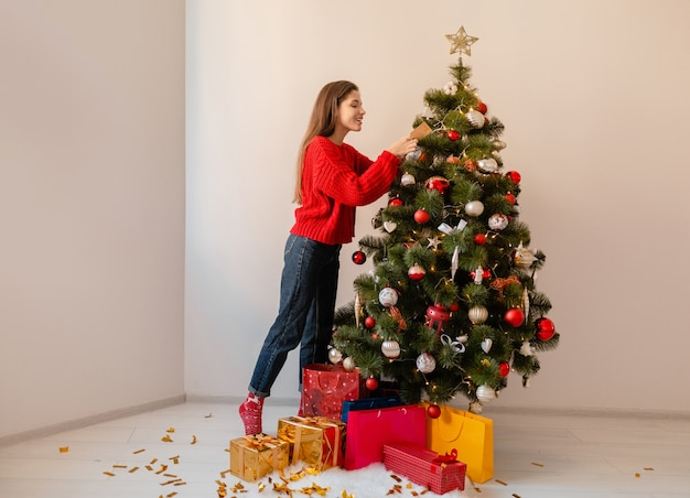 Smiling excited pretty woman in red sweater standing at home decorating christmas tree surrounded with presents and gift boxes