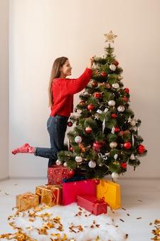 Sorridente donna graziosa eccitata in maglione rosso in piedi a casa che decora l'albero di natale circondato da regali e confezioni regalo