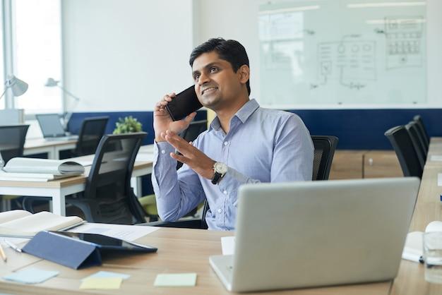 オフィスの机に座って、クライアントや同僚と電話で話している興奮したプロジェクトマネージャーの笑顔