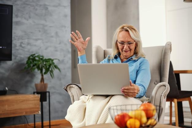 Улыбающаяся, взволнованная старшая женщина, сидящая в кресле у себя дома и смотрящая на ноутбук
