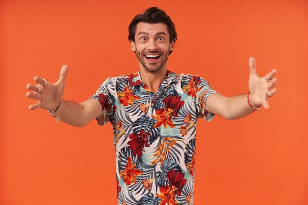 Smiling excited young man with bristle in hawaiian shirt welcoming you and keeps arms opened for hug