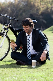 自分の携帯電話をチェック笑顔エグゼクティブ