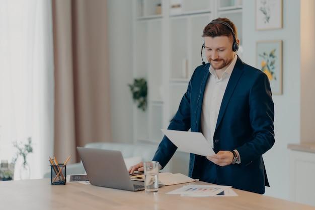Улыбающийся исполнительный менеджер, стоящий возле стола дома и использующий ноутбук, гарнитуру для онлайн-чата с командой, держа документ в руке. бизнесмен, работающий удаленно