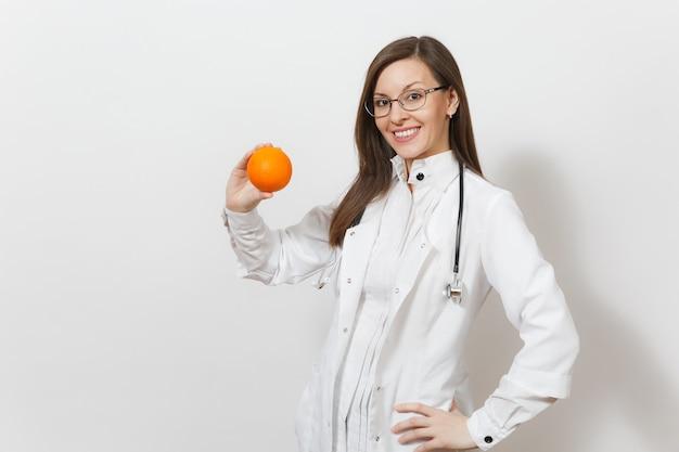 청진 기, 흰색 배경에 고립 된 안경 경험이 풍부한 아름 다운 젊은 의사 여자를 웃 고. 오렌지를 들고 의료 가운에 여성 의사입니다. 의료 인력, 건강, 의학 개념입니다.