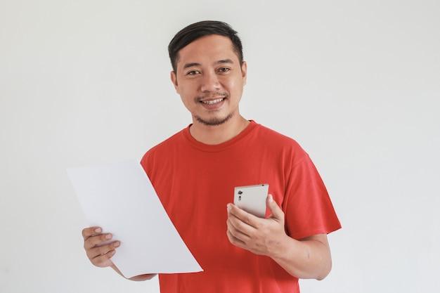 白い白紙とスマートフォンを持って赤いtシャツ探しカメラを身に着けているアジア人男性の笑顔の表情