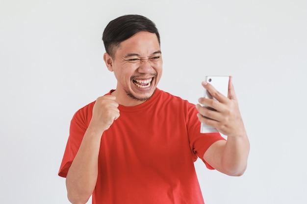 拳の手でスマートフォンを見ている赤いtシャツを着て幸せなアジア人男性の笑顔の表情