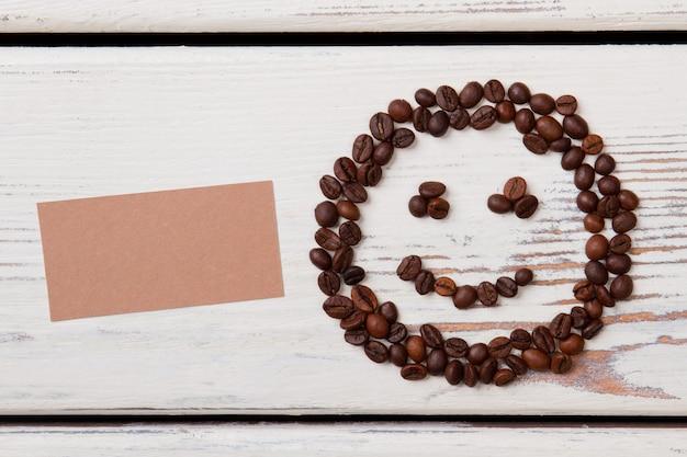Улыбающееся лицо из кофейных зерен и чистый лист бумаги для copyspace. свободное место для вашего текста. белая древесина на поверхности.