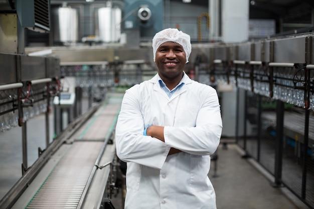 Усмехаясь инженер фабрики стоя с оружиями пересек в фабрику бутылки